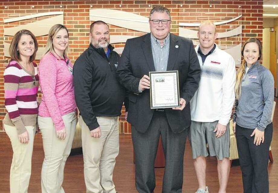 Jacksonville Mayor Andy Ezard (center) recently visited Passavant Area Hospital with a proclamation honoring athletic trainers during National Athletic Trainers Month. Passavant athletic trainers include Monica Huffman (from left), PT, ATC; Larissa Sorrells, PT, DPT, ATC; and Kris Schwiderski, ATC. They were joined by MacMurray College athletic trainers Bryan Langan, ATC; and Jessica Lewis, ATC. Trevor Huffman, MS, PT, SCS, ATC, Passavant's director of Rehabilitation Services; and Illinois College athletic trainers Terry Geirnaeirt, MS, ATC; Sarah Phillips, ATC; and Shawn Woods, MS, ATC; are not pictured. Athletic trainers specialize in the prevention, assessment, treatment and rehabilitation of sports injuries and illnesses. Passavant athletic trainers are members of Team Rehab, an outreach sports rehabilitation and physical therapy service for high school athletes. Team Rehab also provides on-site athletic trainers for weekly school visits, practices and game coverage. Photo: Photo Provided