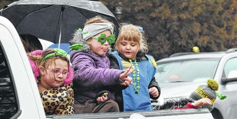 A young Girl Scout from Franklin Troop 6925 tosses out a piece of candy to the crowd on a chilly and soggy Saturday morning for the Jacksonville St. Patrick's Day parade on State Street. Photo: Nick Draper | Journal-Courier