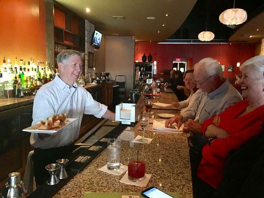 "Downtown Alton's Bossanova Restaurant & Lounge's owner, Russ Smith, behind the bar where he enjoys interacting with customers, presents a favorite menu item — salmon rangoon — to Bossanova ""regulars"" Pat Parker, foreground right, and her Christian Hill neighbors and frequent dining companions, Charlie and JoAnn Stocker. The menu mainstay is included on the dining-and-martini destination's new Asian fusion menu, created by Smith and head chef Dave Smith, who's no relation to the former. The new menu debuted two weeks ago. Photo: Jill Moon