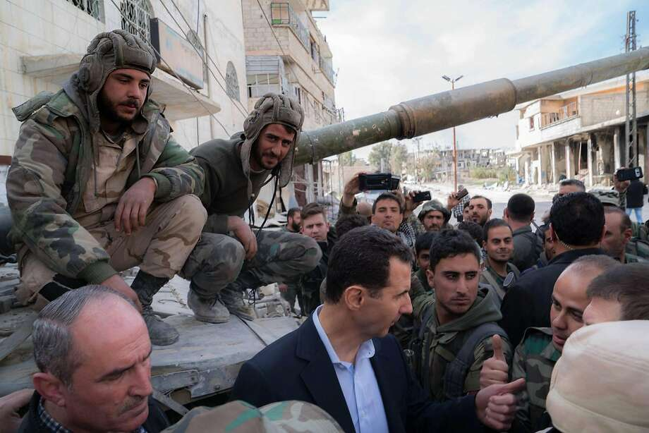 President Bashar Assad (center) visits with government troops near the front line in the east ern Ghouta region in the suburbs of Damascus in an image released by the Syrian Presidency. Photo: HO, AFP/Getty Images