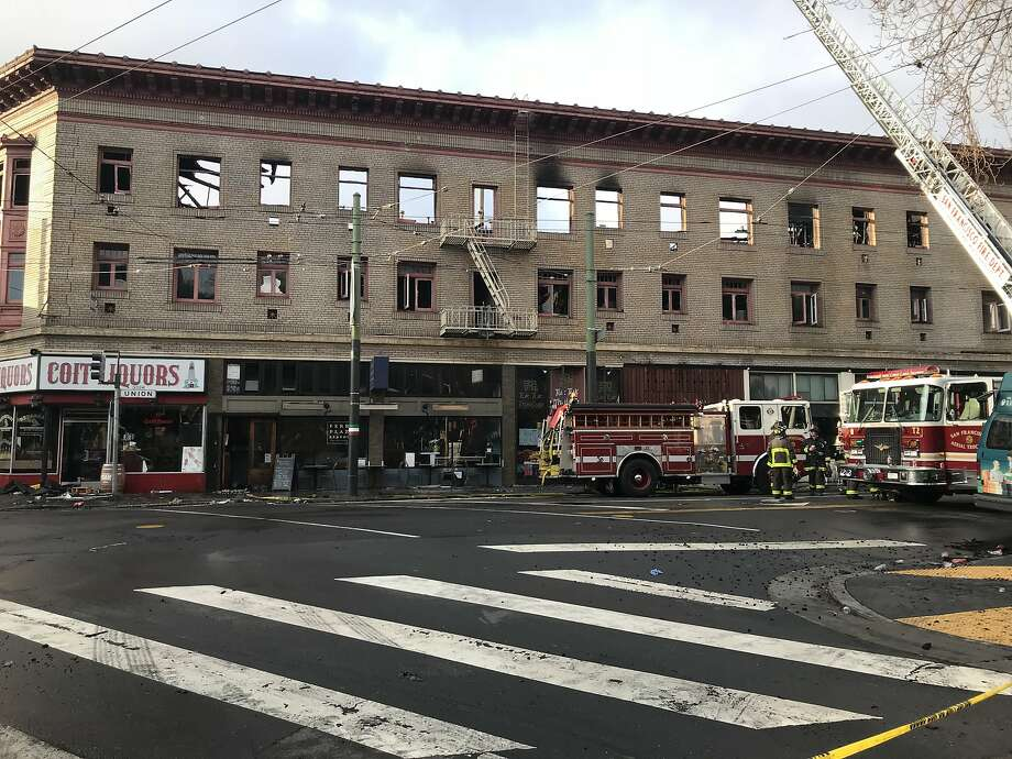 Firefighters hose debris from the streets and check for flareups Sunday after a blaze ripped through a three-story North Beach building the night before. Photo: Sophie Haigney / The San Francisco Chronicle