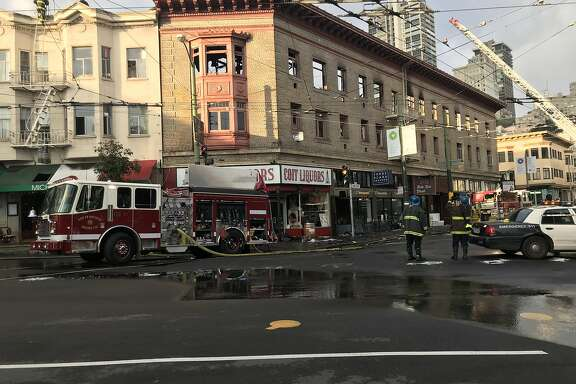 Firefighters were hosing debris from the streets and checking for flare-ups early Sunday, after massive fire�ripped through a three-story North Beach building on Saturday night,