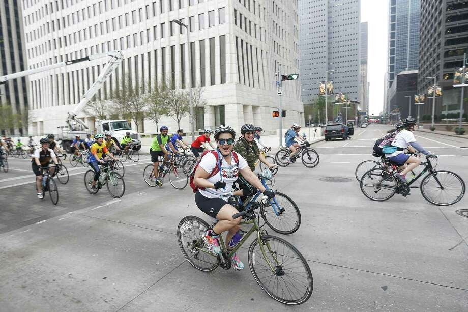 Cyclists head down Smith Street during the start of Tour de Houston presented by Apache Corporation Sunday, March 18, 2018 in Houston. The 60-, 40- or 20-mile fundraising bike ride benefits Houston's Reforestation Program. Photo: Michael Ciaglo / Michael Ciaglo / Houston Chronicle / Michael Ciaglo