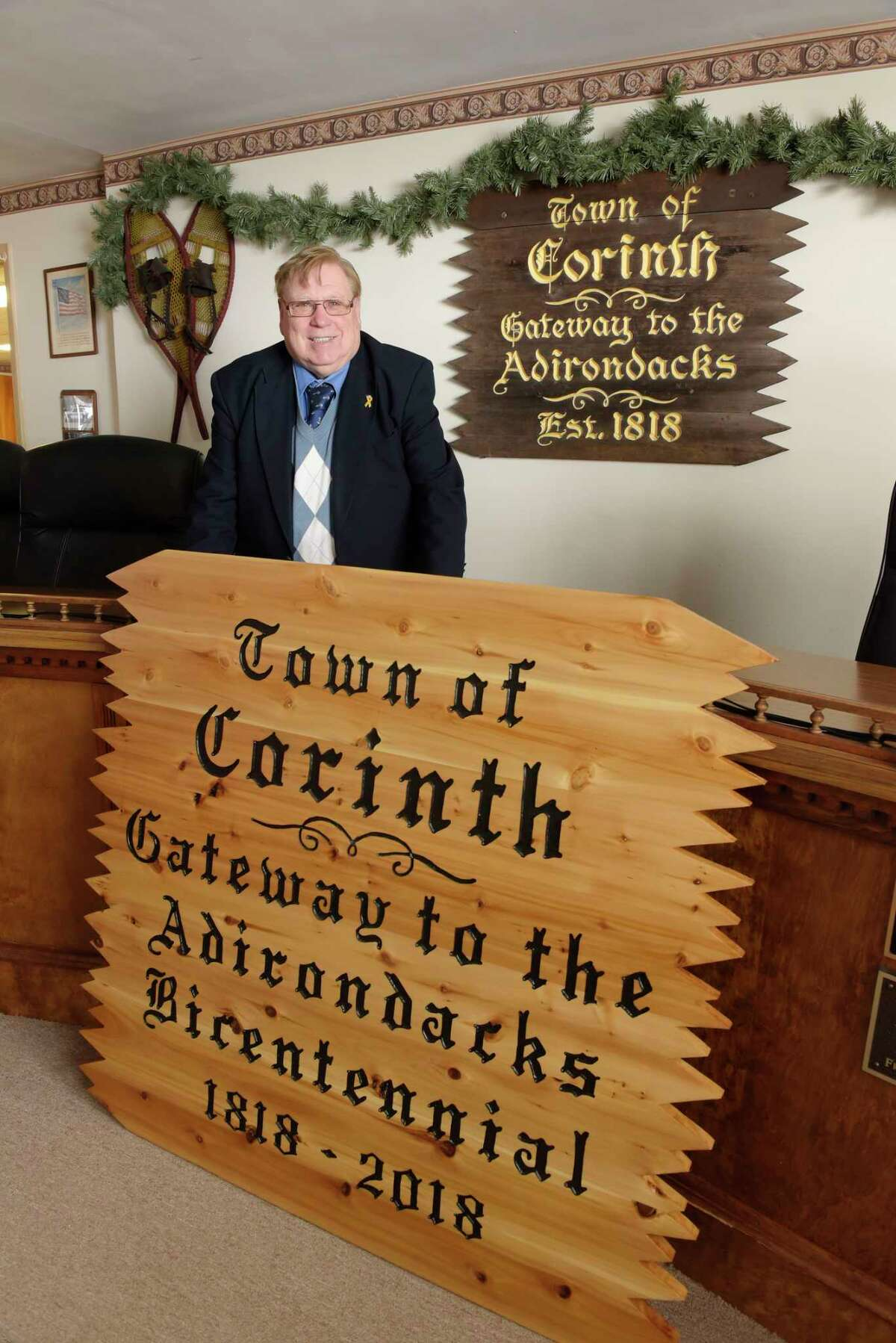 Corinth Town Supervisor Dick Lucia poses with one of the new town signs at Corinth Town Hall on Thursday, March 15, 2018, in Corinth, N.Y. On the wall in the background is the last remaining older town sign. The old sign is over 30 years old, Lucia said. The new signs will be places at the four entrances to the town sometime in the spring. (Paul Buckowski/Times Union)