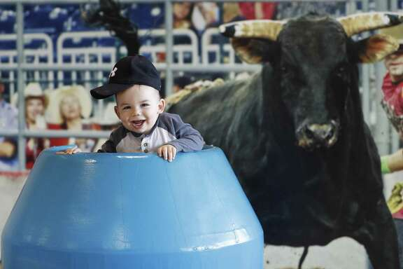 Kyle Beck, 16 months, of Houston, gets his photo taken in the bullfighter barrel at the Houston Livestock Show and Rodeo at NRG Center on March 13.