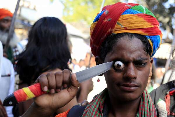 An Indian Muslim devotee performs a stunt by bulging his eyeball with a knife as he takes part in the religious procession for the annual Urs festival at the shrine of Sufi saint Khwaja Moinuddin Chishti in Ajmer, in the Indian state of Rajasthan on March 18, 2018.  Thousands of Sufi devotees from different parts of India travel to the shrine for the annual festival, marking the death anniversary of the Sufi saint.  / AFP PHOTO / HIMANSHU SHARMA        (Photo credit should read HIMANSHU SHARMA/AFP/Getty Images)