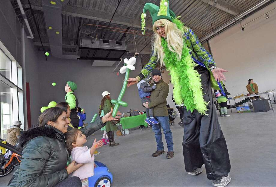 Balloon artist Bibi Farber creates a St. Patrick's Day flower for one-year-old Cassidy Winslow and her mother Ann Marie of North White Plains, New York during a Winter festival at Harbor Point on Saturday, March 17, 2018 in Stamford. Connecticut. Photo: Matthew Brown / Hearst Connecticut Media / Stamford Advocate