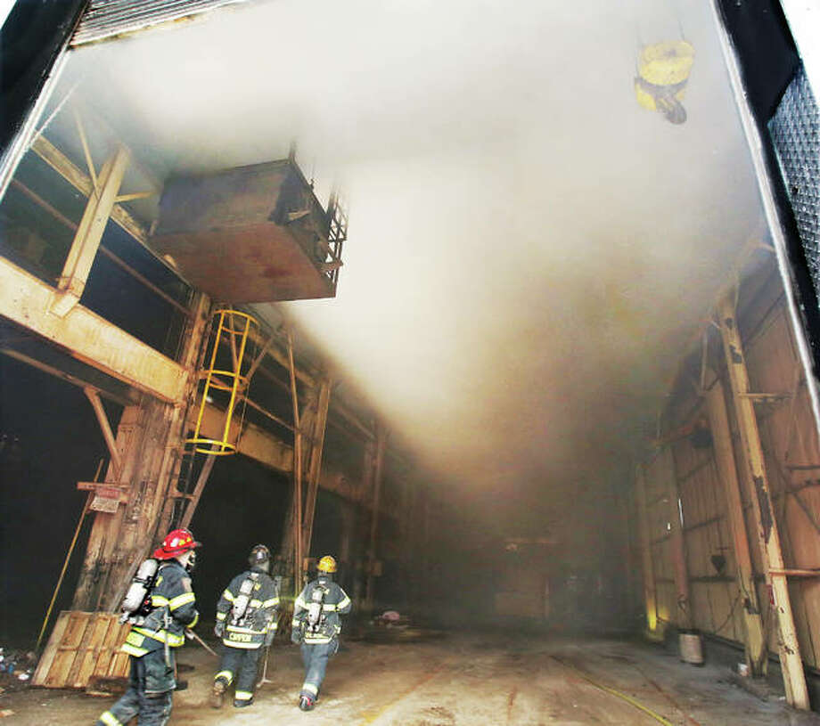A shroud of smoke fills the very tall ceilings of the commercial building at 5th and Piasa Sunday morning as Alton firefighters head to the corner of the building where wooden pallets and a machine were on fire. The building was the former Lenhardt Tool & Die Company building. The Illinois State Fire Marshal was called to the scene as the fire may be suspicious in nature, and if so would be the third suspicious fire in just over a week in Alton. A commercial box alarm was struck for the fire, bringing ladder trucks from East Alton and Wood River, as firefighters saw heavy smoke coming from the block-long structure when they arrived. Photo: John Badman | The Telegraph