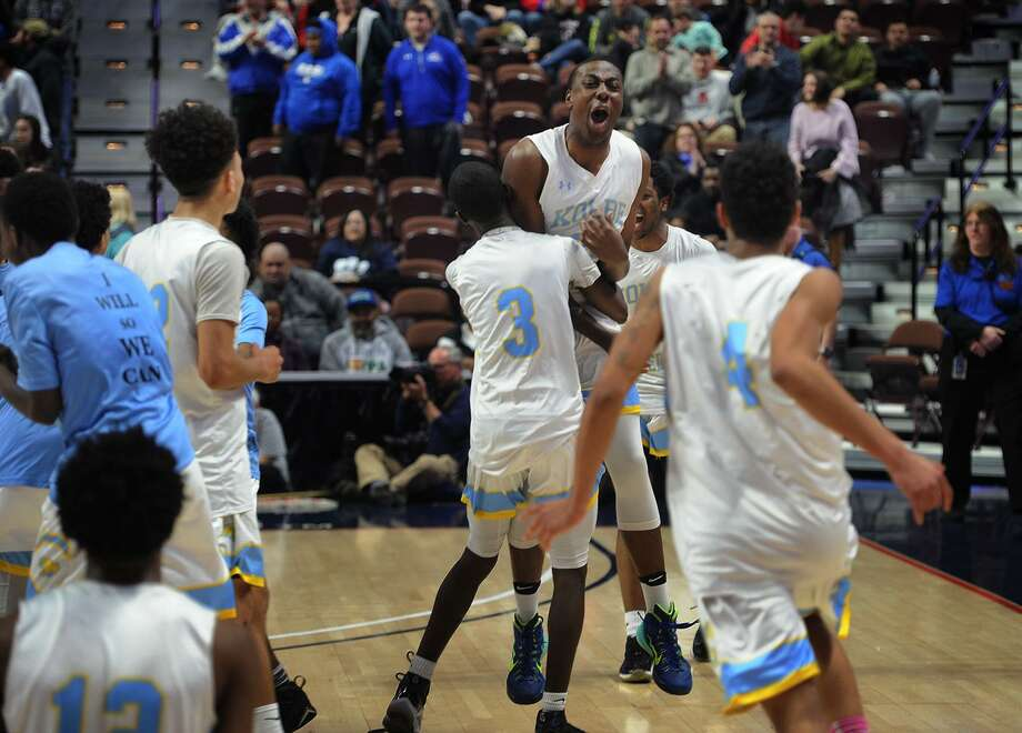 Kolbe Cathedral's Jason Smith, facing, is hugged by teammate Nazire Vereen as his team storms he court following their 55-40 victory over Rocky Hill in the Division IV Boys Basketball Championship at the Mohegan Sun Arena in Montviille, Conn. on Sunday, March 18, 2018. Photo: Brian A. Pounds / Hearst Connecticut Media / Connecticut Post