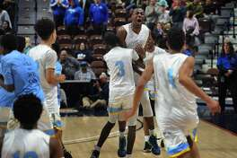 Kolbe Cathedral's Jason Smith, facing, is hugged by teammate Nazire Vereen as his team storms he court following their 55-40 victory over Rocky Hill in the Division IV Boys Basketball Championship at the Mohegan Sun Arena in Montviille, Conn. on Sunday, March 18, 2018.