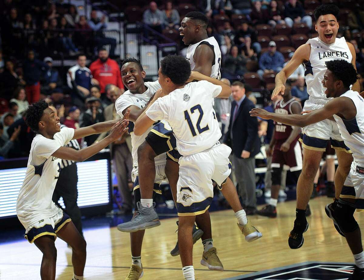 Notre Dame of Fairfield players celebrate following their 65-60 victory over Sacred Heart in the Division I boys basketball championship game at the Mohegan Sun Arena in Montviille on Sunday.