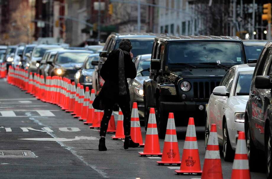 A pedestrian cuts between cars waiting in line during rush hour traffic on Hudson Street near the entrance to the Holland Tunnel, Friday, March 16, 2018, in New York. Prospects appear to be dimming for the latest proposal to impose new tolls on motorists entering the busiest parts of Manhattan. A state panel recommended tolls of as much as $11 or more as a way to address gridlock while raising money for transit. But lawmakers are balking, with some suggesting a more limited fee for taxis, limos and ride-hailing services like Uber instead. (AP Photo/Julie Jacobson) Photo: Julie Jacobson / Copyright 2018 The Associated Press. All rights reserved.