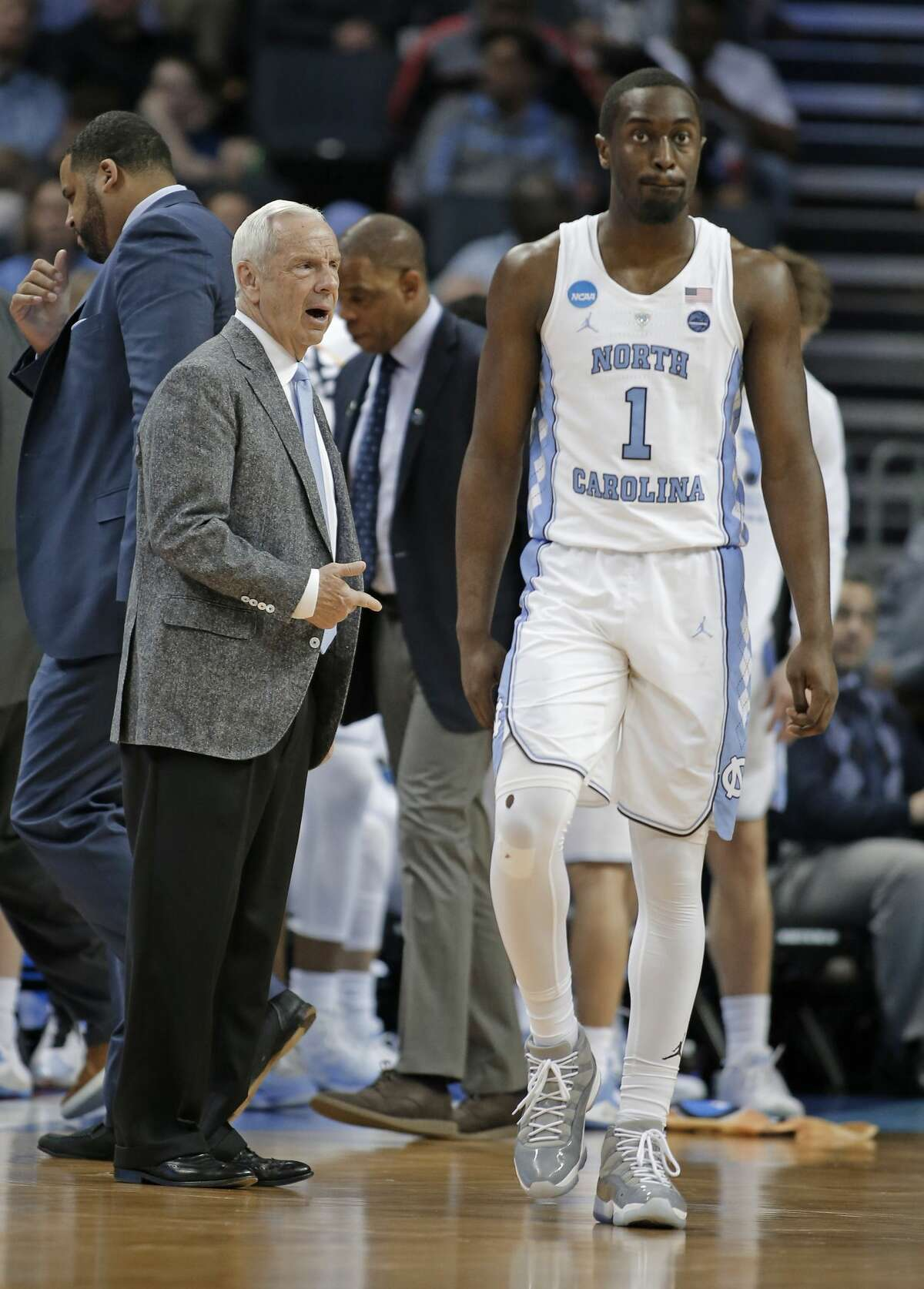 North Carolina's Theo Pinson (1) walks past head coach Roy Williams during the second half of a second-round game against Texas A&M in the NCAA men's college basketball tournament in Charlotte, N.C., Sunday, March 18, 2018. (AP Photo/Bob Leverone)
