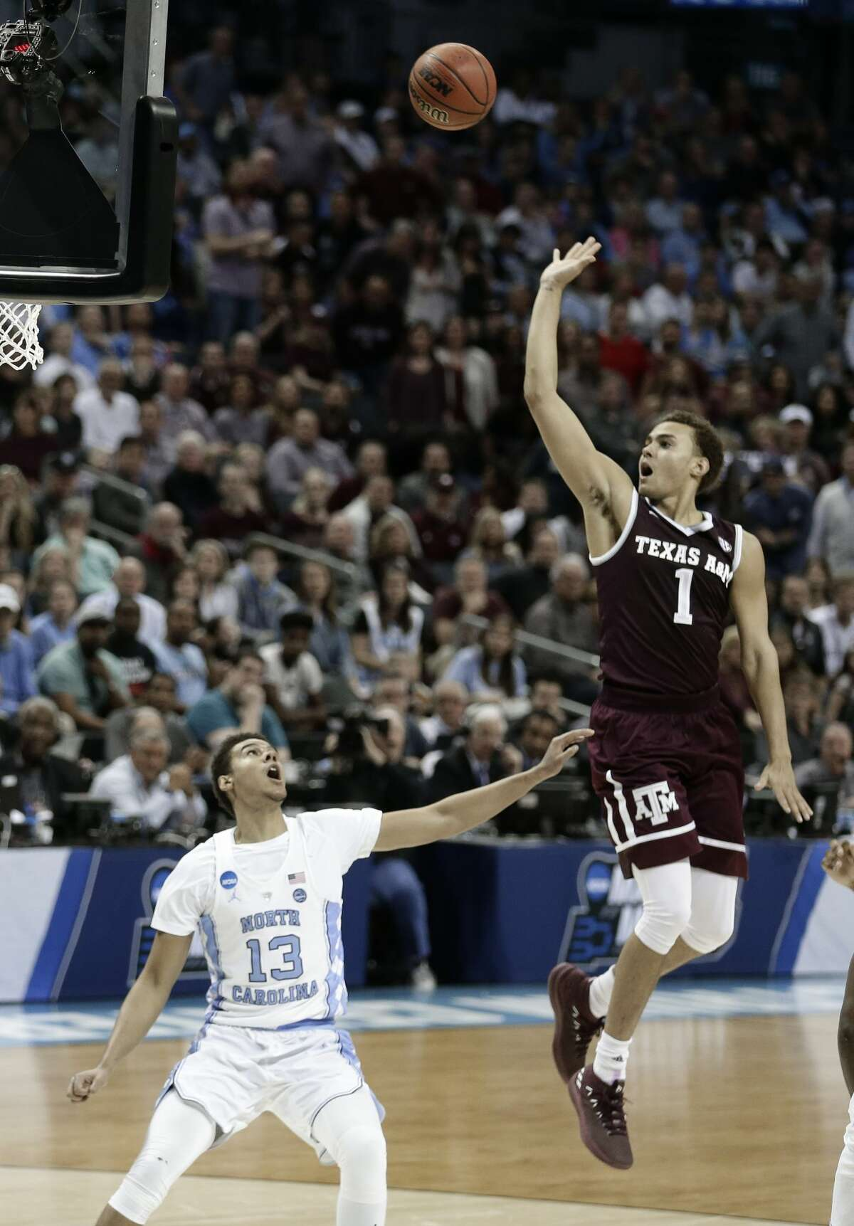 Texas A&M's DJ Hogg (1) shoots over North Carolina's Cameron Johnson (13) during the first half of a second-round game in the NCAA men's college basketball tournament in Charlotte, N.C., Sunday, March 18, 2018. (AP Photo/Gerry Broome)