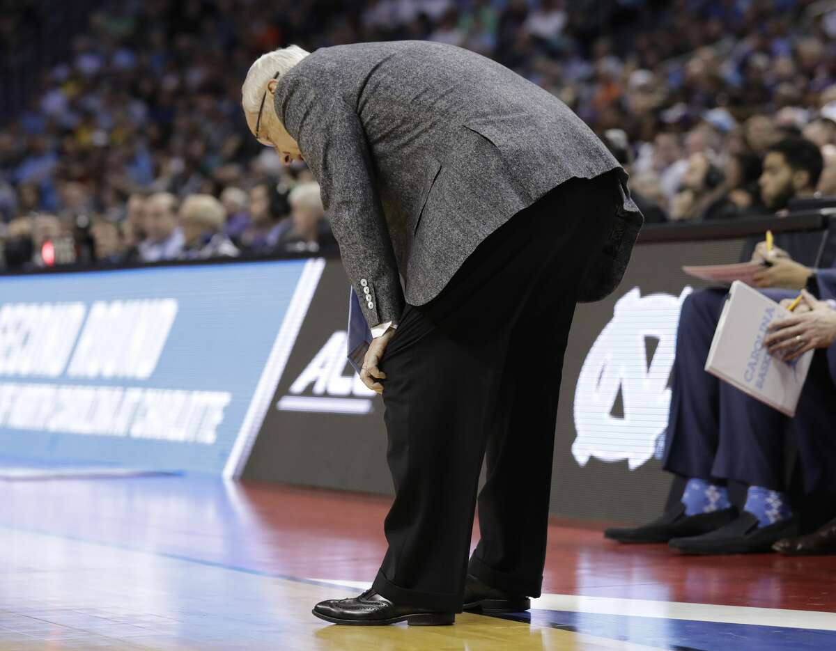 North Carolina head coach Roy Williams bends over in the final minutes during the second half of a second-round game against Texas A&M in the NCAA men's college basketball tournament in Charlotte, N.C., Sunday, March 18, 2018. (AP Photo/Gerry Broome)
