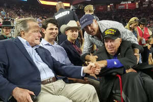 President George H.W. Bush, left, shook hands Sunday with 99-year-old World War II veteran Sidney Walton at the Houston Livestock Show and Rodeo.