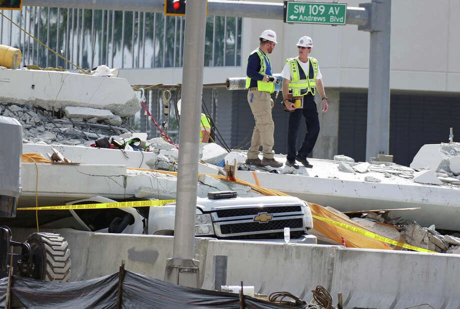 """Inspectors walks over what remains of a pedestrian bridge near Florida International University, Sunday, March 18, 2018 near Miami. As crews removed bodies from beneath a collapsed pedestrian bridge Saturday, a victim's uncle raged against what he called the """"complete incompetence"""" and """"colossal failure"""" that allowed people to drive beneath the unfinished concrete span. The unfinished bridge collapsed on Thursday killing six people. (C.M. Guerrero/The Miami Herald via AP) Photo: C.M. GUERRERO / Miami Herald"""