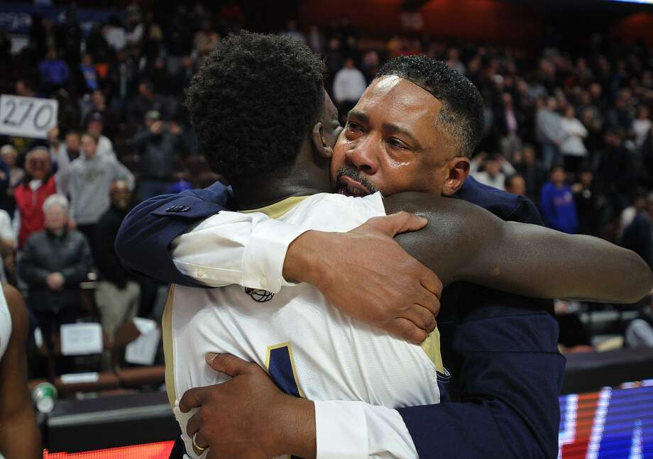 With tears in his eyes, Notre Dame of Fairfield coach Chris Watts hugs player Damion Medwinter following the Lancers' 65-60 victory over Sacred Heart in the Division I championship on Sunday at the Mohegan Sun Arena in Montville. Photo: Brian A. Pounds / Hearst Connecticut Media / Connecticut Post