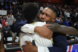 With tears in his eyes, Notre Dame of Fairfield coach Chris Watts hugs player Damion Medwinter following the Lancers' 65-60 victory over Sacred Heart in the Division I championship on Sunday at the Mohegan Sun Arena in Montville.