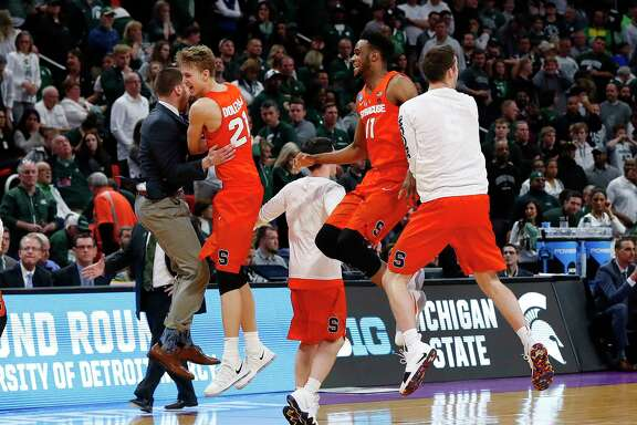 Syracuse players, including Marek Dolezaj (21) and Oshae Brissett (11), celebrate after holding off Michigan State 55-53 on Sunday.
