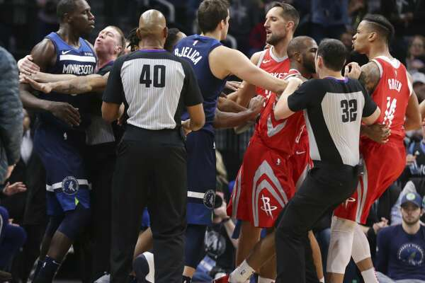 Minnesota Timberwolves center Gorgui Dieng (5) and Houston Rockets forward Gerald Green (14) are restrained in the fourth quarter of an NBA basketball game Sunday, March 18, 2018, in Minneapolis. Green was ejected on the play as the Rockets defeated the Timberwolves 129-120. (AP Photo/Andy Clayton-King)
