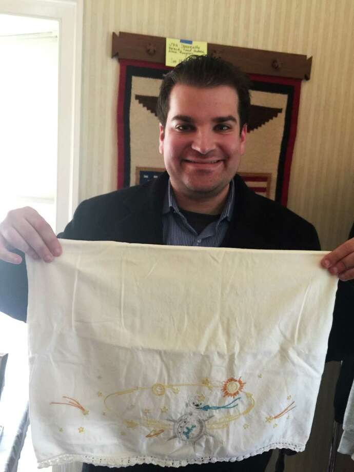 CORRECTS DAY OF AUCTION TO MARCH 8 FROM MARCH 9 - This undated photo provided by Adam Sackowitz, of Queens, New York, shows him displaying an embroidered pillowcase with celestial bodies on it that belonged to the late John Glenn. Sackowitz purchased the pillowcase for $2,500 at a March 8, 2018, estate sale in Potomac, Md. He hopes to donate it to a historic site in Glenn's native Ohio. (Courtesy of Adam Sackowitz via AP) / Adam Sackowitz