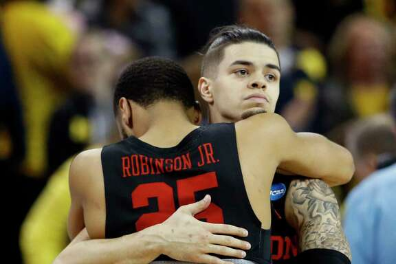 UH guard Rob Gray hugs Houston Galen Robinson Jr. (25) after the team's loss to Michigan.