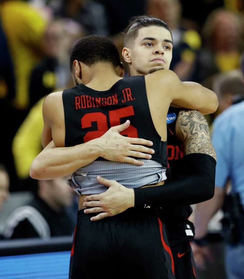 Guard Rob Gray hugs teammate Galen Robinson Jr. (25) after UH's loss to Michigan. Photo: Charlie Riedel, STF / Copyright 2018 The Associated Press. All rights reserved.