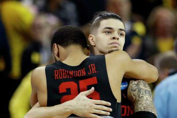 Guard Rob Gray hugs teammate Galen Robinson Jr. (25) after UH's loss to Michigan.