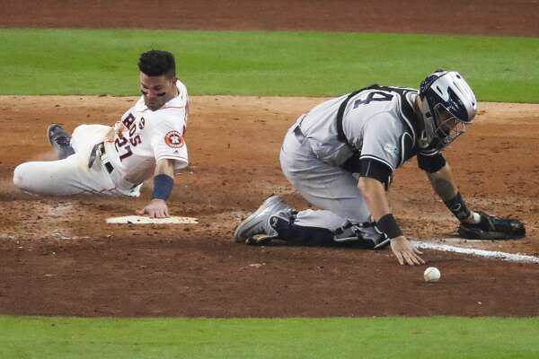 New York Yankees catcher Gary Sanchez (24) bobbles the ball as Houston Astros second baseman Jose Altuve (27) scores the winning run off of a double by Houston Astros shortstop Carlos Correa (1) during the ninth inning as the Houston Astros beat the New York Yankees 2-1 in Game 2 of the ALCS at Minute Maid Park Saturday, Oct. 14, 2017 in Houston. ( Michael Ciaglo / Houston Chronicle)