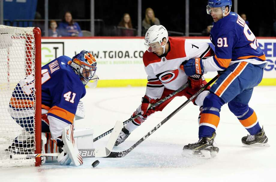 New York Islanders goaltender Jaroslav Halak (41) of Slovakia makes a save as New York Islanders center John Tavares (91) defends Carolina Hurricanes center Derek Ryan (7) the first period of an NHL hockey game in New York, Sunday, March 18, 2018. (AP Photo/Kathy Willens) Photo: Kathy Willens / Copyright 2018 The Associated Press. All rights reserved.