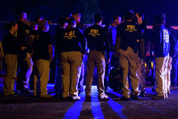 FBI agents meet at the scene of an explosion in Austin, Texas, Sunday, March 18, 2018. At least a few people were injured in another explosion in Texas' capital late Sunday, after three package bombs detonated this month in other parts of the city, killing two people and injuring two others. (Nick Wagner/Austin American-Statesman via AP)