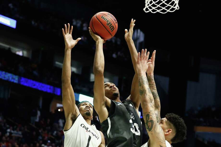 NASHVILLE, TN - MARCH 18:  Josh Hall #33 of the Nevada Wolf Pack shoots the ball over Jacob Evans #1 and Jarron Cumberland #34 of the Cincinnati Bearcats during the second half in the second round of the 2018 Men's NCAA Basketball Tournament at Bridgestone Arena on March 18, 2018 in Nashville, Tennessee.  (Photo by Andy Lyons/Getty Images) Photo: Andy Lyons / 2018 Getty Images