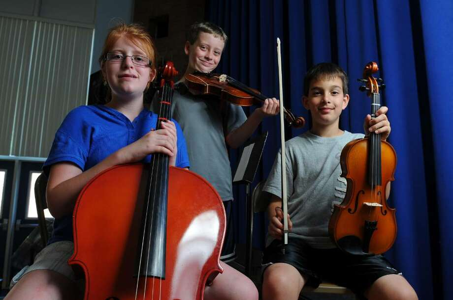 "Ashley Wemble, Cameron Kaercher, center, and Joseph Molloy are among the members of the Blue Creek school orchestra who will perform in a spring concert Tuesday night at Shaker High School.  One piece, ""The Green Drakkoman,"" is in memory of Ben Stowell, a fourth grader who died of cancer in October. ( Philip Kamrass / Times Union) Photo: PHILIP KAMRASS"