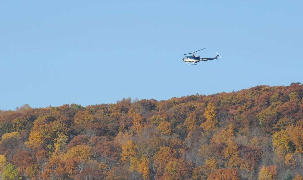 A New York State Police helicopter hovers over the site of a small-plane crash on Whipstock Mountain, northwest of the Bennington, Vt., airport on Monday Oct. 26, 2009. (Skip Dickstein / Times Union)