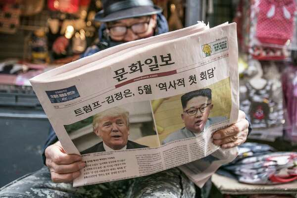 A man reads a copy of the Munhwa Ilbo newspaper featuring President Trump and North Korean leader Kim Jong Un on the front page in Seoul on March 9.