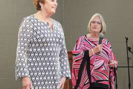 Sheena Bass (right) introduces the first model, Glenda Shuttlesworth at the San Jacinto County Women's League fashion show on March 8.