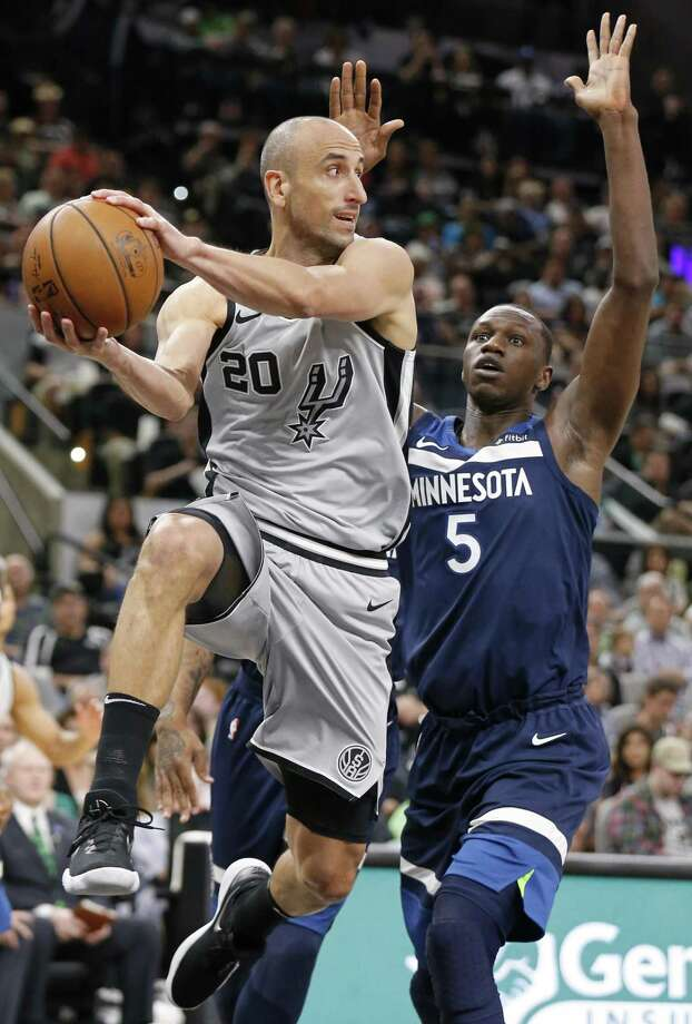 Spurs guard Manu Ginobili looks to pass around the Timberwolves' Gorgui Dieng on Saturday. Photo: Edward A. Ornelas / San Antonio Express-News / © 2018 San Antonio Express-News