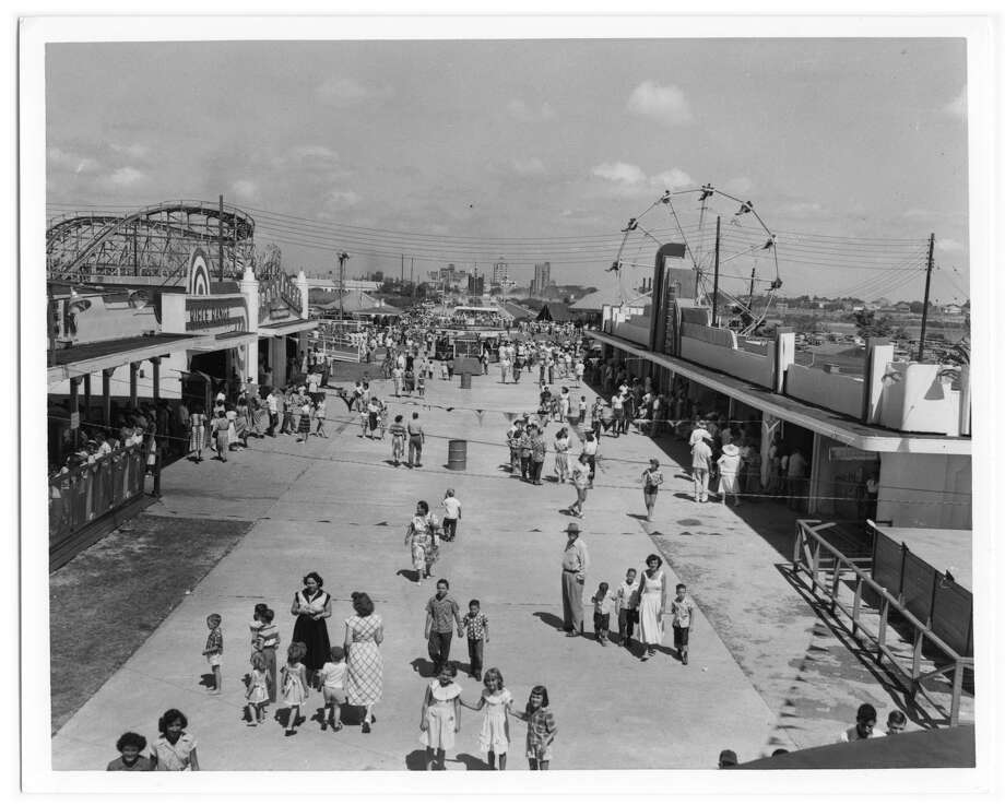 Photograph of the midway of Pleasure Island in Port Arthur. There are a number of booths along the sides of the midway. A ferris wheel and roller coaster are also visible. In the far distance, the tall buildings of downtown Port Arthur can be seen. Many groups of people are walking the midway, playing games, buying food, and waiting in line for rides. Photo: This photograph is Part Of The Collection Entitled: Rescuing Texas History, 2009 and Was Provided By Port Arthur Public Library to The Portal To Texas History, A Digital Repository Hosted By The UNT Libraries