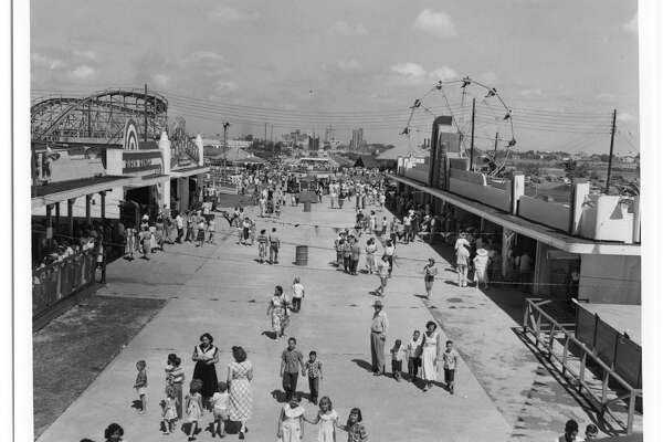 Photograph of the midway of Pleasure Island in Port Arthur. There are a number of booths along the sides of the midway. A ferris wheel and roller coaster are also visible. In the far distance, the tall buildings of downtown Port Arthur can be seen. Many groups of people are walking the midway, playing games, buying food, and waiting in line for rides.