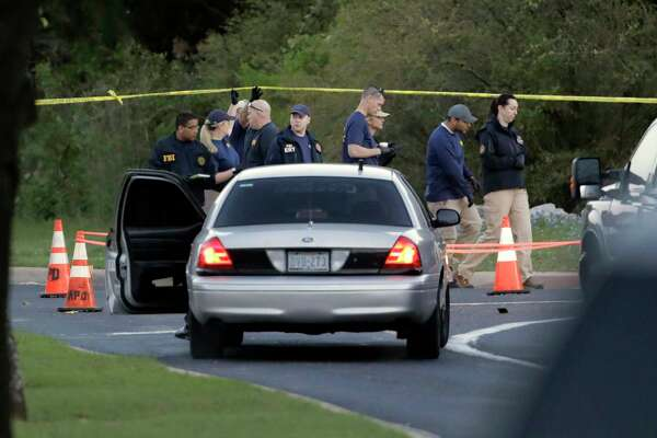 Officials work and stage near the site of Sunday's deadly explosion, Monday, March 19, 2018, in Austin, Texas. Police warned nearby residents to remain indoors overnight as investigators looked for possible links to other package bombings elsewhere in the city this month.