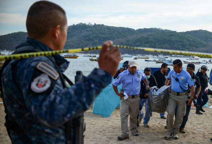 Forensic personnel and police officers carry the body of a murdered man, at Caletilla beach, in the touristic city of Acapulco, Guerrero State, Mexico, on March 18, 2018. Guerrero is one of Mexico's poorest and most violent states, where a lucrative drug trade has flourished. / AFP PHOTO / FRANCISCO ROBLES        (Photo credit should read FRANCISCO ROBLES/AFP/Getty Images)