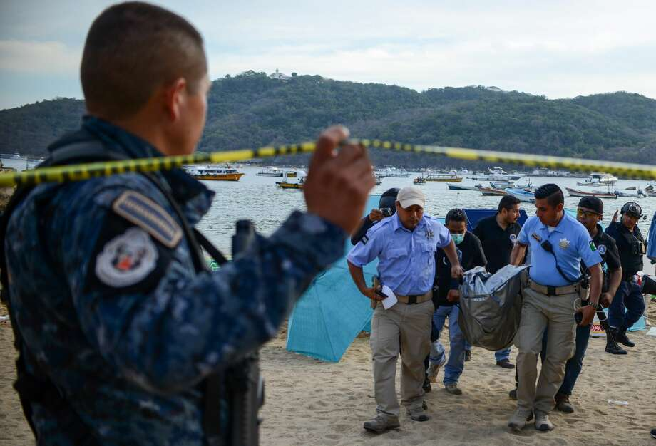 Forensic personnel and police officers carry the body of a murdered man, at Caletilla beach, in the touristic city of Acapulco, Guerrero State, Mexico, on March 18, 2018. Guerrero is one of Mexico's poorest and most violent states, where a lucrative drug trade has flourished. / AFP PHOTO / FRANCISCO ROBLES        (Photo credit should read FRANCISCO ROBLES/AFP/Getty Images) Photo: FRANCISCO ROBLES/AFP/Getty Images