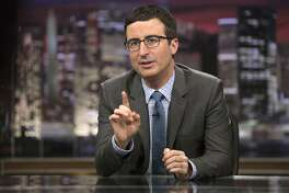 "In this April 2014 image released by HBO, host John Oliver speaks during ""Last Week Tonight with John Oliver,"" in New York. Oliver, who subbed for Jon Stewart as host of ""The Daily Show"" last summer and began his own HBO weekly show in April, often devotes about half of his 30 minutes to a single topic below the headlines. His subsequent report questioning the pageant's scholarship program was the latest example of how Oliver has quickly moved beyond his roots at ""The Daily Show"" to produce something distinctive, and usually hilarious. (AP Photo/HBO, Eric Liebowitz)"