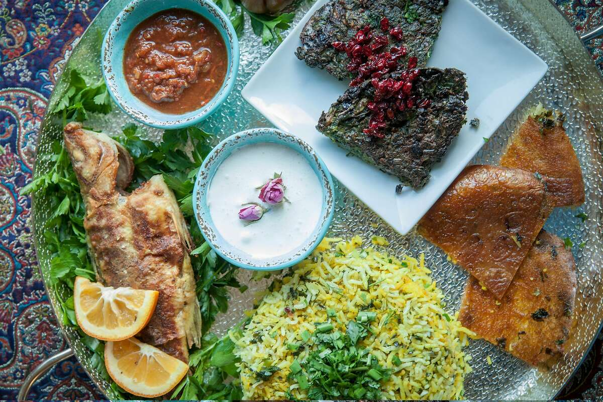 Various Persian dishes severed on a large plater created by Aisan Parnia at her home in Hercules, California, USA 27 Feb 2018. Mohi safeed (white fish) top, Kuku Sabzi (eggs, herbs and barbaries) on small white plate, Sabzi polo (rice, saffron, herbs, with tahdig layer at the bottom with lavash breaded) left and bottom.