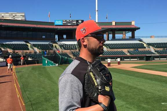 Former Giant Travis Ishikawa looks watches the Giants practice during a workout at Scottsdale Stadium on Monday.