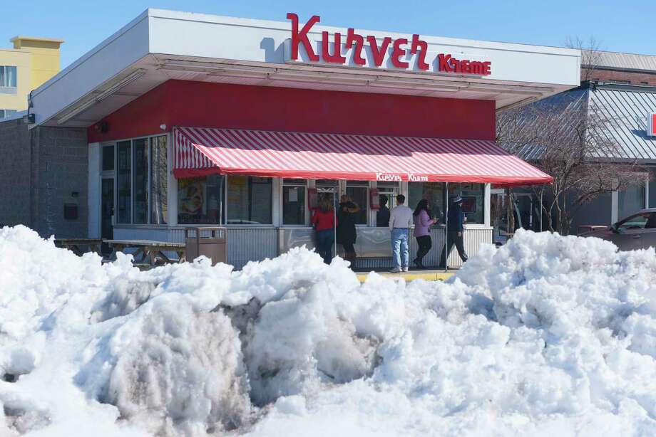 Snow banks line the parking lot as customers get their ice cream during opening day at the Kurver Kreme on Monday, March 19, 2018, in Colonie, N.Y. This is the 66th year of operation for the ice cream stand. The stand will be open Monday through Friday from 11:00am to 9:00pm, Saturday Noon to 9:00pm and Sunday 1:00pm to 9:00pm. Kurver also has for the second year, Dole vegan frozen treat.  (Paul Buckowski/Times Union) Photo: PAUL BUCKOWSKI, Albany Times Union / (Paul Buckowski/Times Union)