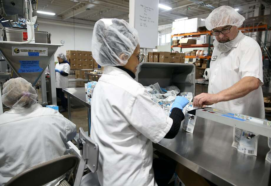 Production manager Rick Decost (right) checks packages of chocolate at Ocho candy factory. Photo: Liz Hafalia / The Chronicle