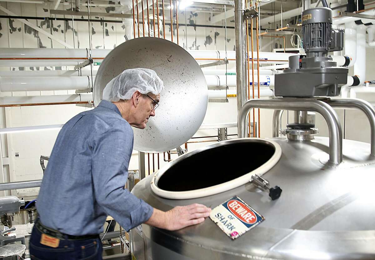 Ocho founder Denis Ring shows the milk chocolate holding vat at the factory.