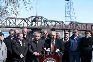 Senator Charles Schumer surrounded by representatives from various construction/trade unions and other elected officials holds a press conference at the Corning Preserve on Monday, March 19, 2018, in Albany, N.Y. Senator Schumer held the event to announce his plan to push for a major infrastructure proposal. In the background is the Livingston Avenue Rail Bridge, which is in need to repair Senator Schumer said.   (Paul Buckowski/Times Union)